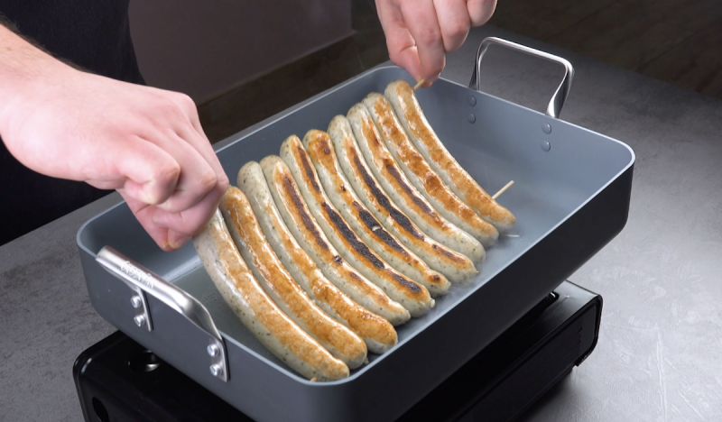 мясные колбаски жарят на сковороде