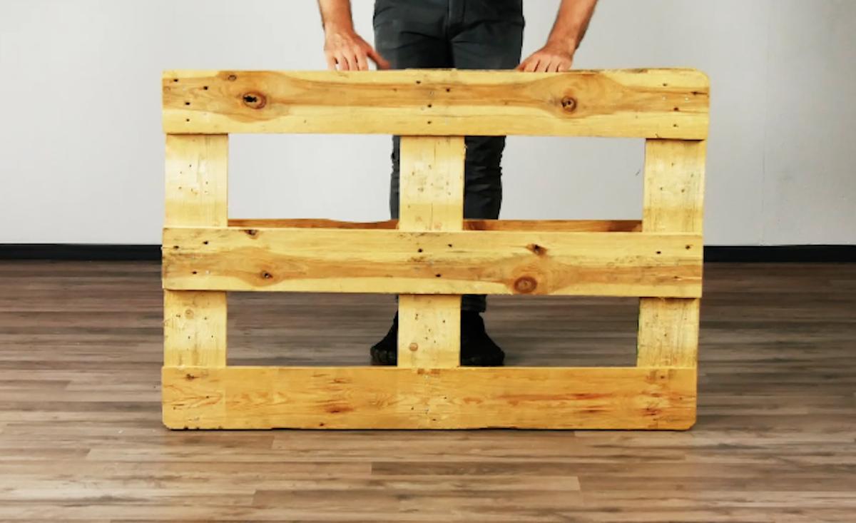 мужчина держит деревянный поддон